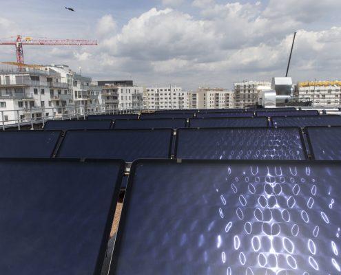 Ansicht von Solarzellen mit Hochhäusern im Hintergrund